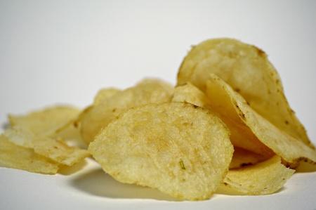 A pile of plain potato chips sits on a plain background Stock Photo - 12247122