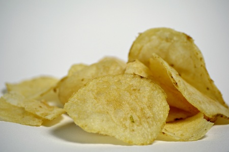 A pile of plain potato chips sits on a plain background Stock Photo - 12247122