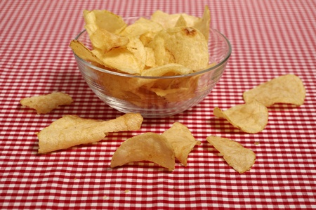Potato chips in a glass bowl on a red and white check table cloth Stock Photo - 12247128