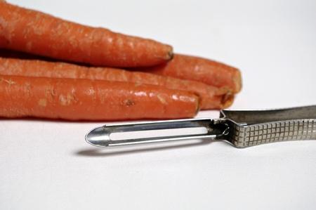 Carrots provide the backdrop for a potato peeler. Imagens