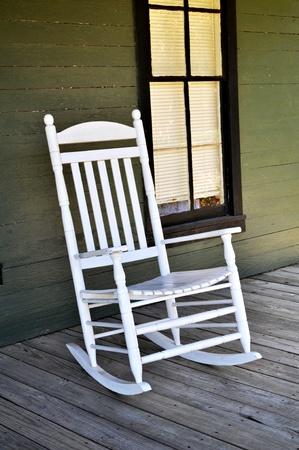 현관: 흰색 나무 흔들 의자는 현관에 앉아있다 스톡 사진