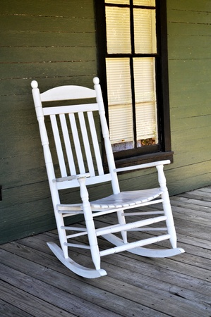 A white wooden rocking chair is sitting on the front porch