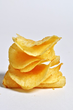 A stack of potato chips sits on a plain white background. Stock Photo - 12247154