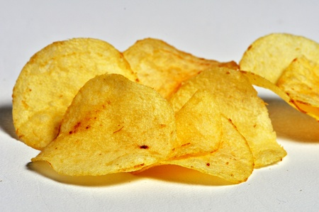A small pile of crunchy potato chips lay on a plain background. Stock Photo - 12253529