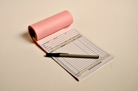 A open receipt book and pen are laying on a table. Stock Photo