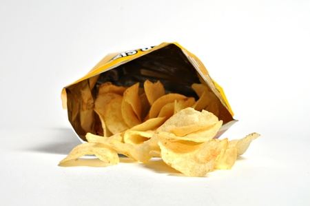 A bag of potato chips is laying on its  side with chips spilling out on itside.