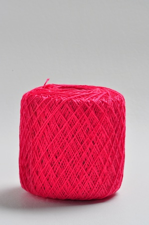 A ball of red yarn is on a plain white background. photo