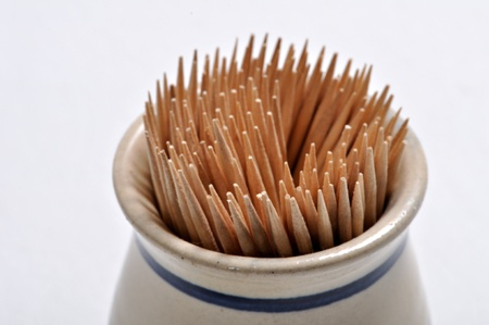 toothpick: Toothpicks in a toothpick holder on a plain background.
