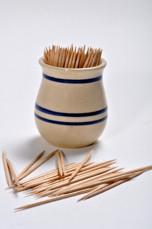 Wooden toothpicks and the toothpick holder are on a white background.