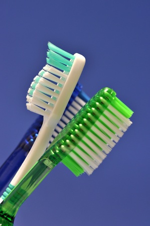 Three toothbrushes are on a blue background Stock Photo