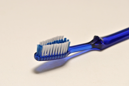 A single blue tooth brush lies on a white background.