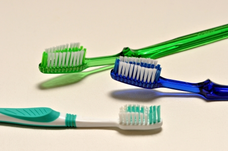 Three tooth brushes are laying on a white back ground. Stock Photo - 14019276