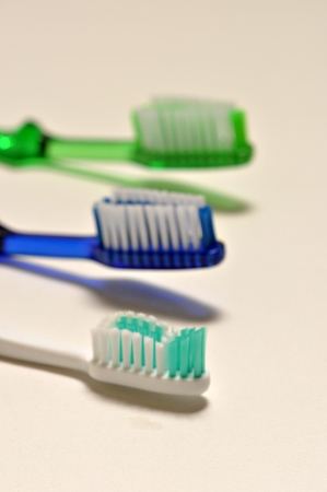 Three tooth brushes are laying on a white back ground. Stock Photo