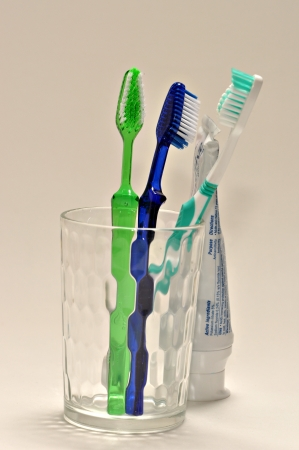 Three tooth brushes and a tube of tooth paste are on a white background