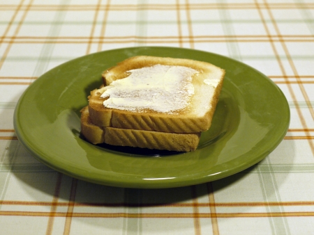 Two slices of butter toast sit on a green saucer.