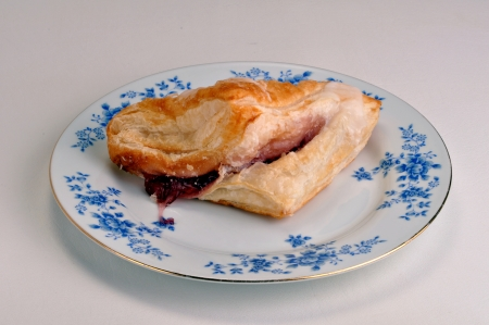 turnover: Cherry turnover on a saucer on a white background.