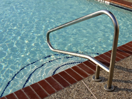 hand rail: A image of a metal hand rail at a outdoor swiming pool. Editorial