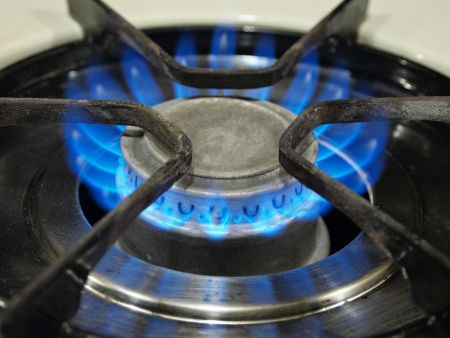 gas stove: A blue flame is burning brightly on top of a propane burning stove.