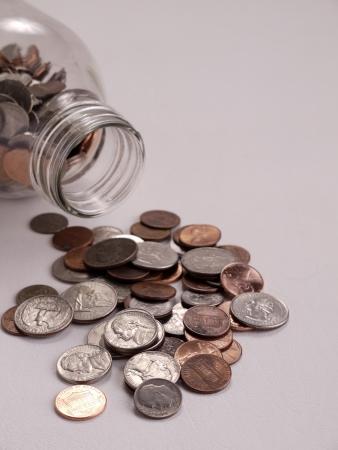 Amerikaanse munten gemorst uit op een tafelblad uit een melkkannetje wordt gebruikt als een bank.