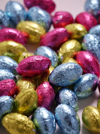 A photo of a pile of brightly wraped chocolate Easter eggs on a plain background.