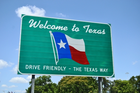 A Welcome to Texas road sign set against a light blue background showing the state flag Stock Photo