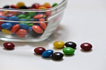 Caramelos de chocolate que pone en un top blanco y en un plato de vidrio Foto de archivo - 19609745