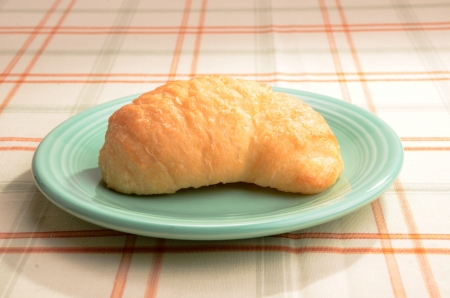 A single crossiant is on a blue saucer