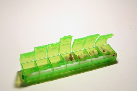 A green colored weekly pillbox sitson a white background with a assortment of pills in the box.