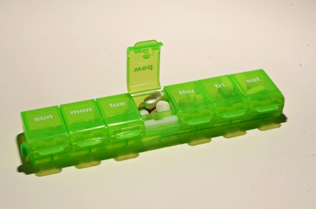 A green pillbox with pills on a white background.