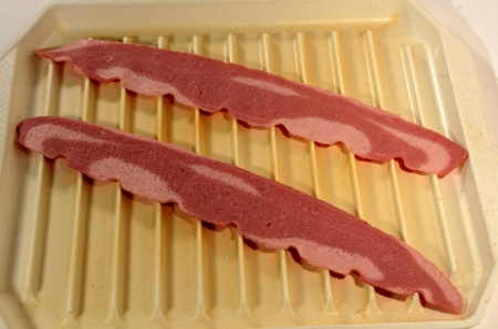 uncooked bacon: Two slices of raw turkey bacon sits on a microwaveable dish. Stock Photo