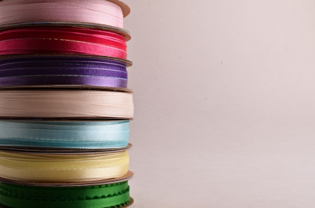 A stack of  spools of ribbon on a white background.