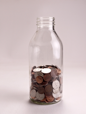 A half full jar of American coins sits on a white background. photo