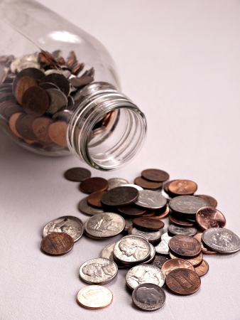 American coins are spilling out from a tipped over jar onto a white background. Banco de Imagens