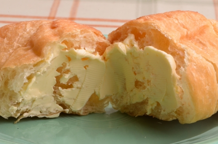 A closeup view of a croissant with butter spread on it.