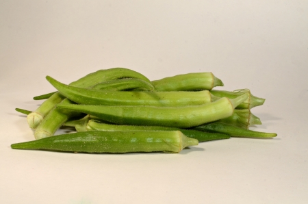 A small pile of okra is laying on a white background awaiting to be fixed for dinner.