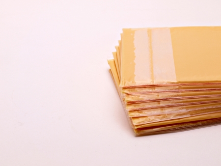 A stack of American cheese slices is laying on a white background. Stock fotó
