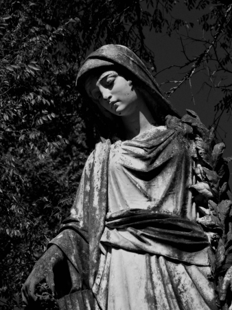 grave site: A stone statue of a angel marks a grave site