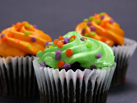 A image of three Halloween cupcakes readyto be eaten.