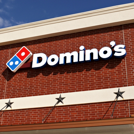 A Dominos Pizza sign on a building in Tyler Texas.