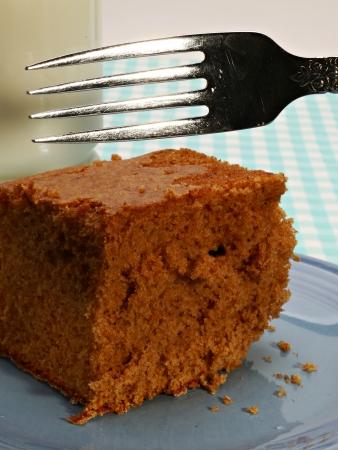 spicecake: Una rebanada de caseros spicecake es en un plato azul con un vaso de leche