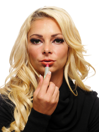 A attractive blond woman is applying lipstick