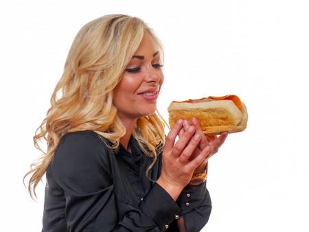 A attractive blond woman is looking at a deli sandwich.