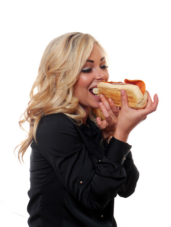 A attractive blond woman is eating a deli style sandwich.