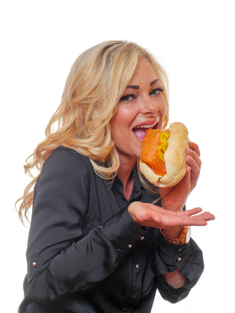 A blond haired woman is eating a deli styled sandwich. Stock Photo