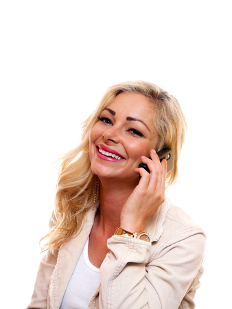 A woman is smiling while talking on her cell phone.