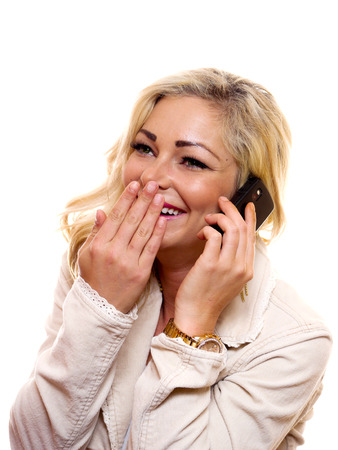 A woman is laughing whille talking on her cell phone.