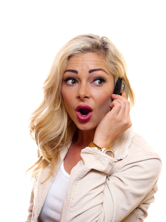 A woman has a surprised look on her face while talking on the cell phone.