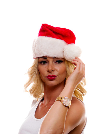 A attractive woman is wearing a Santa Claus cap.