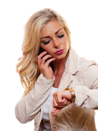 A attractive woman is looking at her watch while talking on her cell phone. Фото со стока