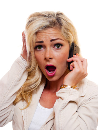 A attractive blonde woman is shocked while talking on cell phone.